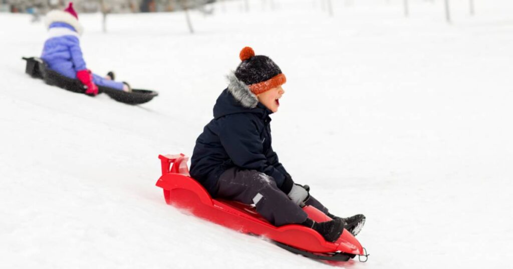 two kids sledding down a hill