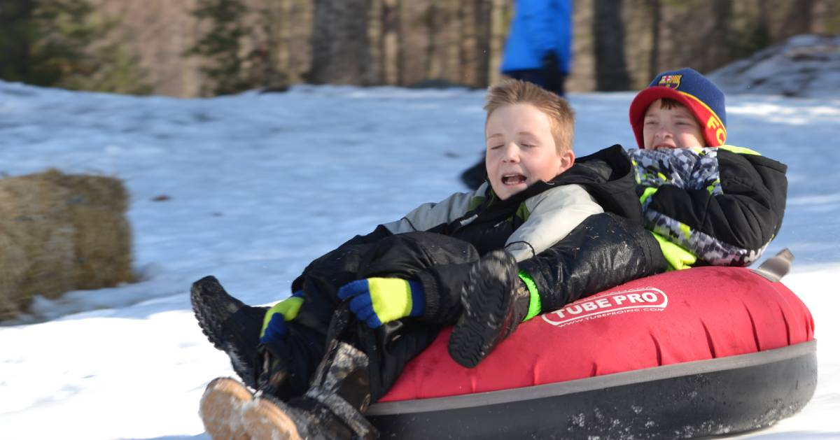 two boys in a snow tube going down a hill