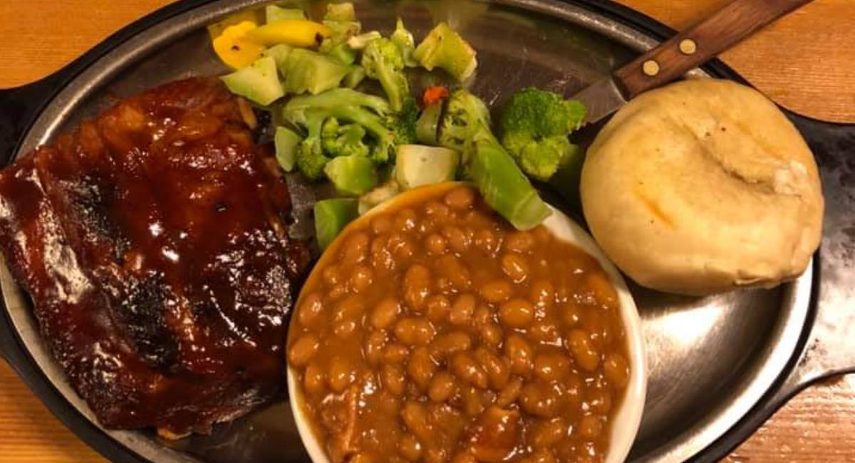 ribs, baked beans, and steamed veggies on a platter