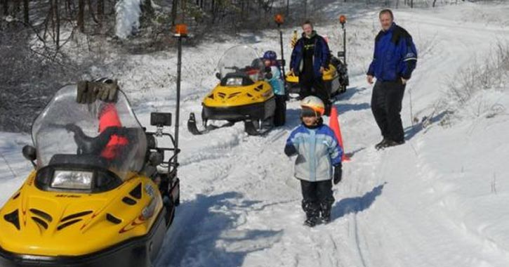kid and people near snowmobiles