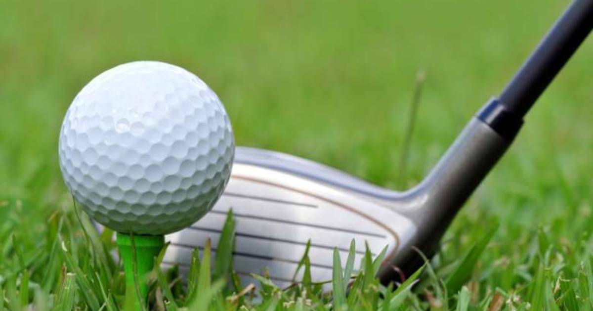 close up view of a golf ball and club