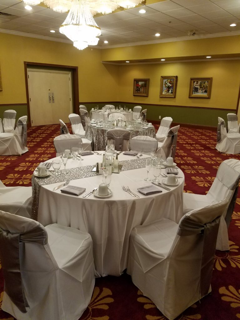 Silver Sequin Runner w/ Silver Majestic Sashes and Napkins w/ Ivory Majestic Tablecloths and White Poly Chair Covers