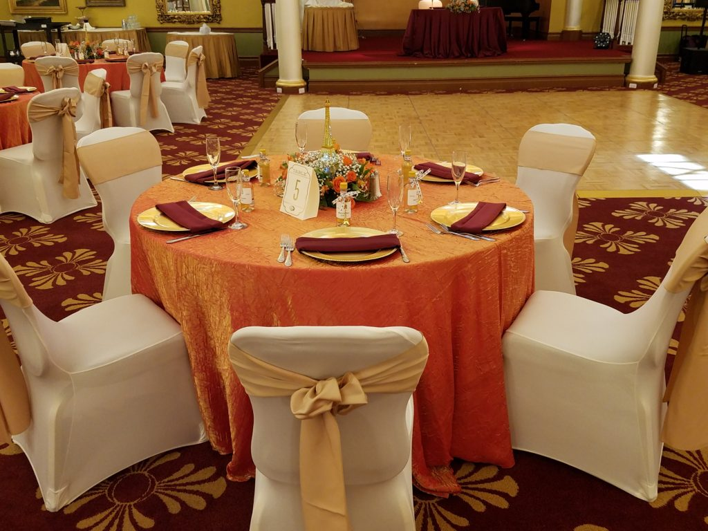 Persimmon Crush Tablecloth with Champagne Satin Sashes and Burgundy Poly Napkins and White Spandex Chair Covers with Gold Chagers
