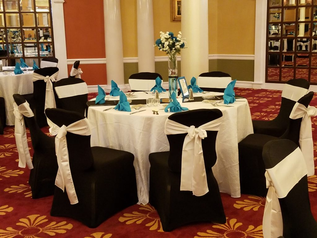 White Satin Sashes and Ivory Tablecloths w/ Turquoise Napkins and Black Runners