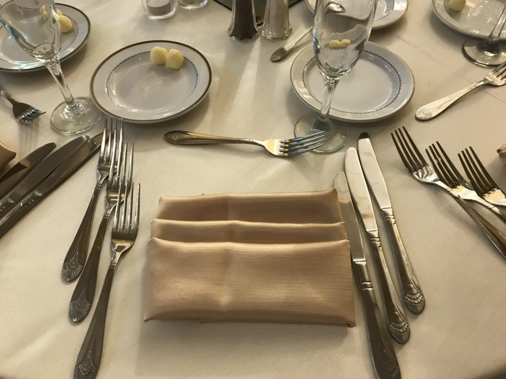 White Poly Tablecloths w/ Gold Satin Sashes and Napkins and White Spandex Chair Covers