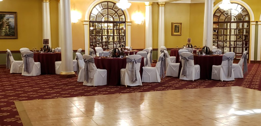 Silver Majestic Sashes with Burgundy Poly Tablecloths and Rust Napkins with White Poly Chair Covers