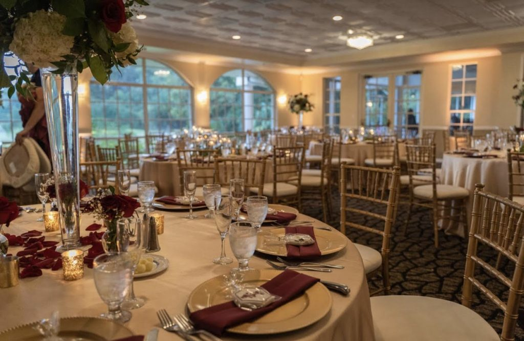 Champagne Majestic Tablecloths with Burgundy Satin Napkins and Gold Chargers