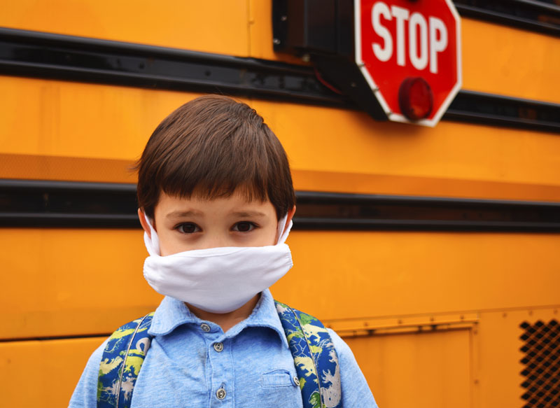 Child with mask in front of school bus