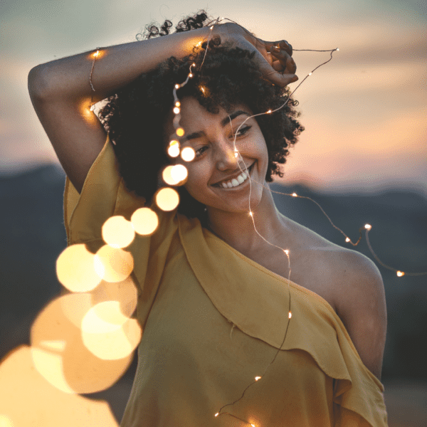 smiling woman with a string of lights