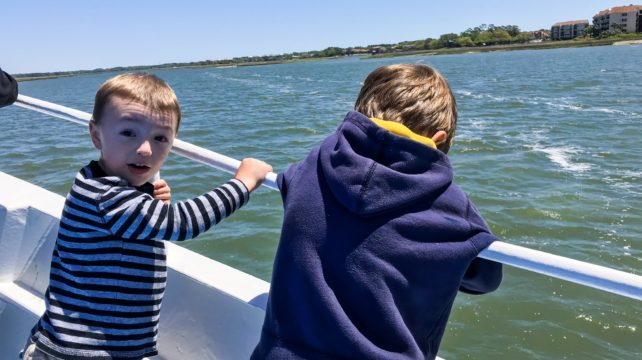 Boys look out at the ocean from a dolphin boat.