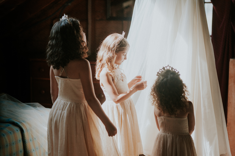 flower girls looking at wedding dress, flower girl touching wedding dress, leanne marshall dress hanging