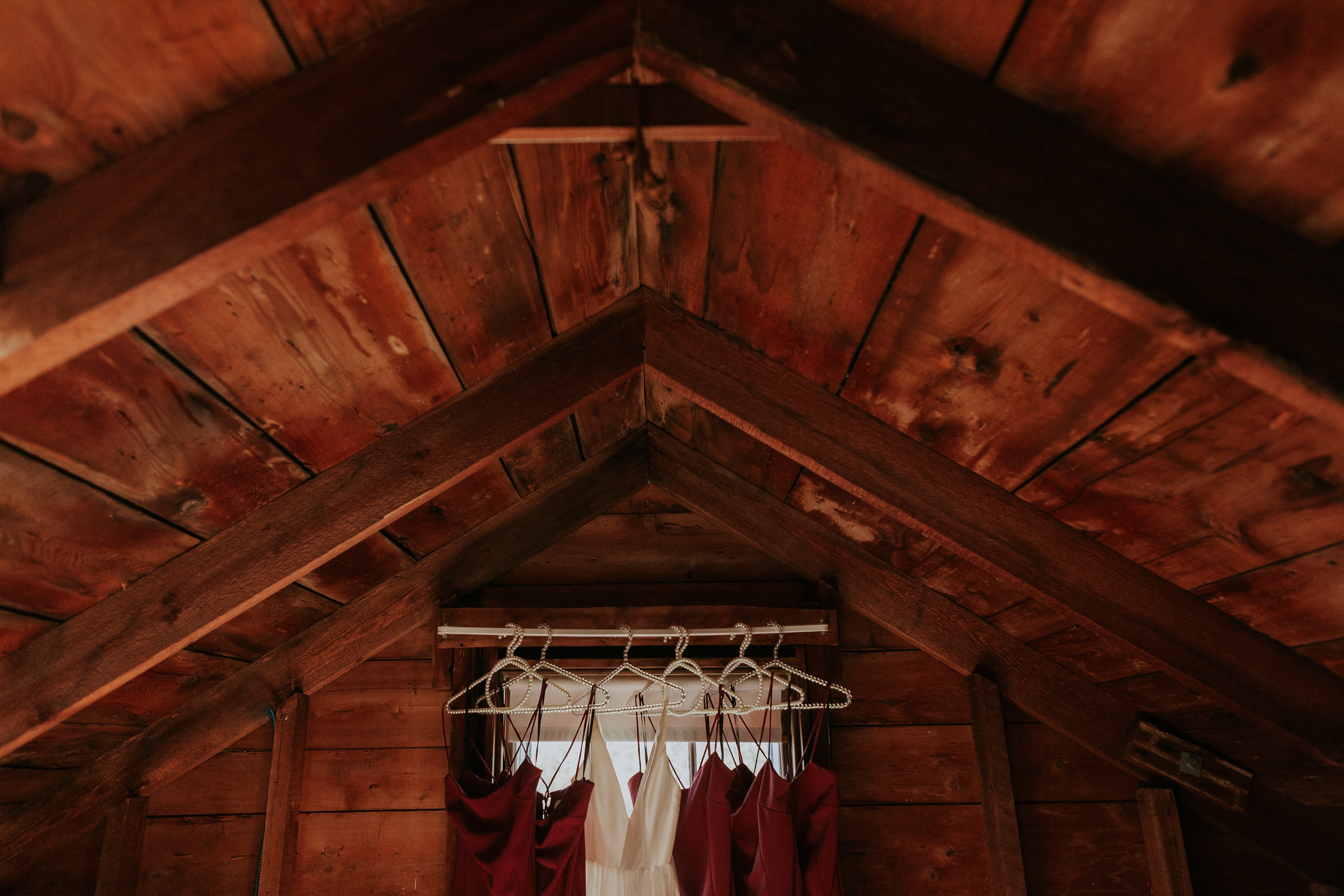 dresses hanging in attic, wedding dress and red bridesmaid dress, getting ready Martha's Vineyard