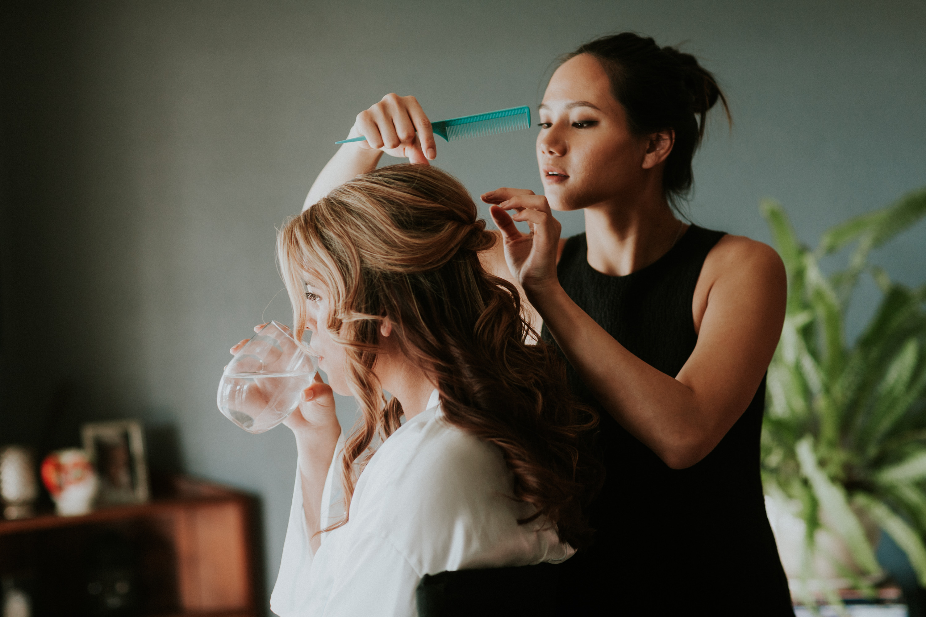 bride getting hair done, bride drinking water while getting hair done