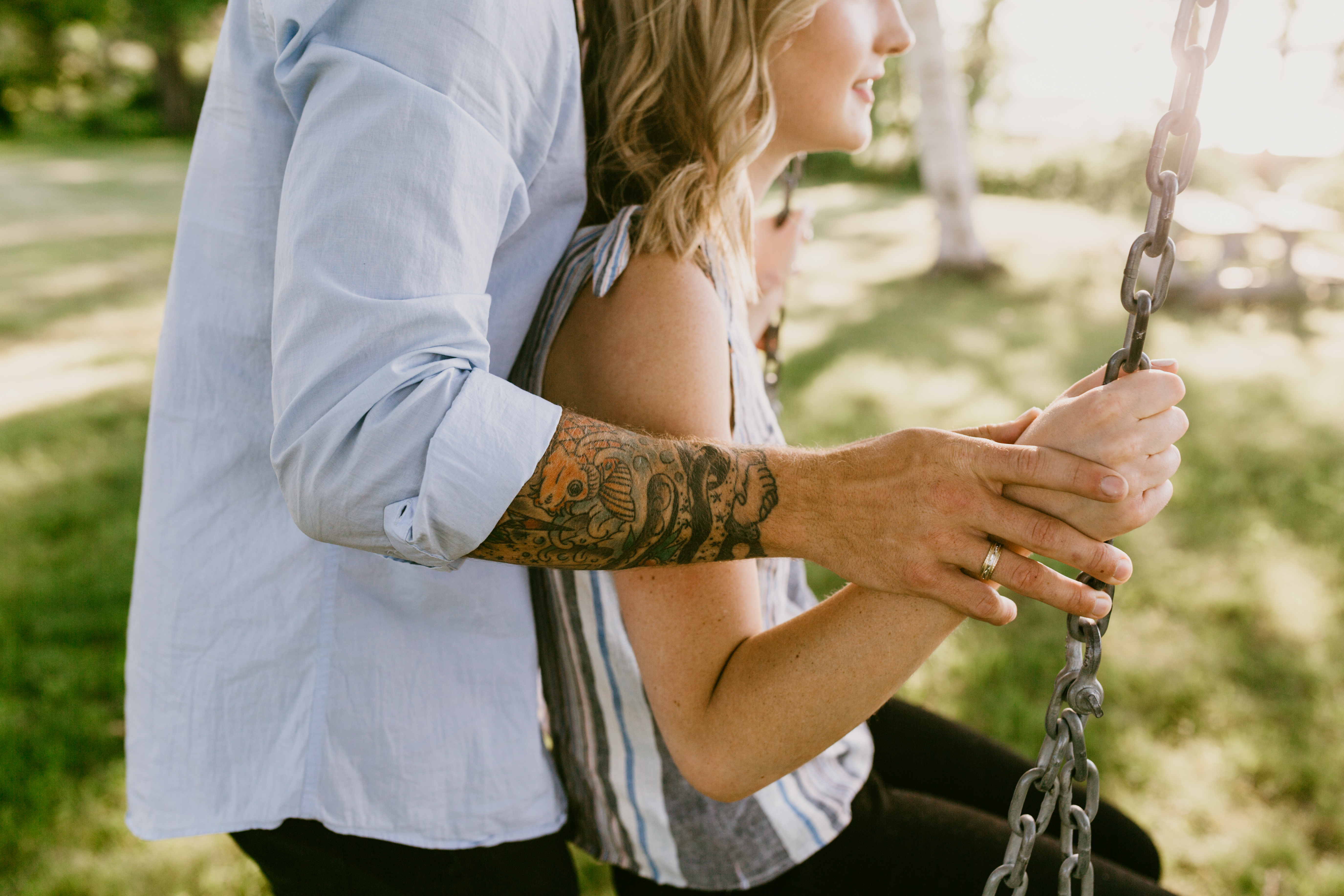 guy with tatto pushing fiance on swing