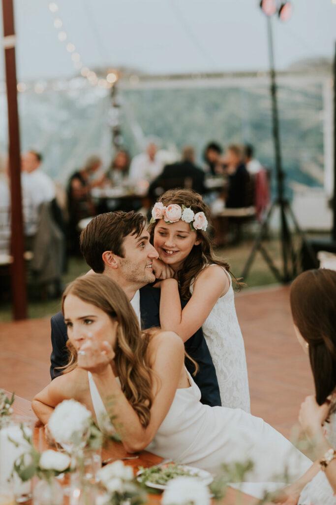 flower girl hugs groom at Cape Cod wedding reception