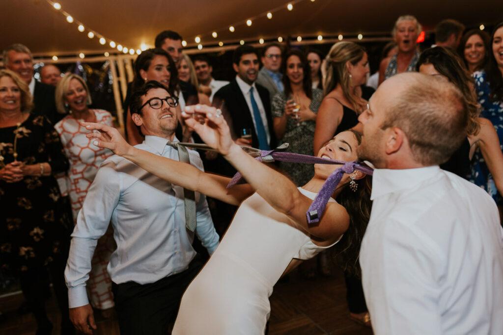 bride limbos under neckties at Cape Cod wedding reception