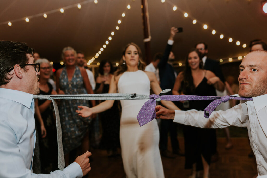 bride prepares to limbo under necktie limbo line