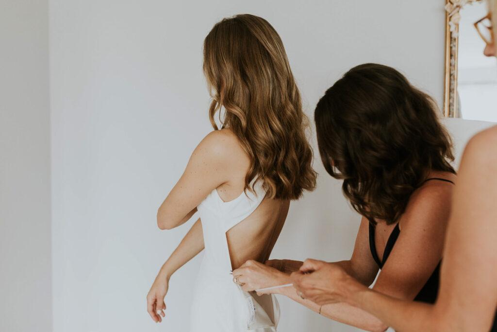 bridemaids do up bride's dress buttons