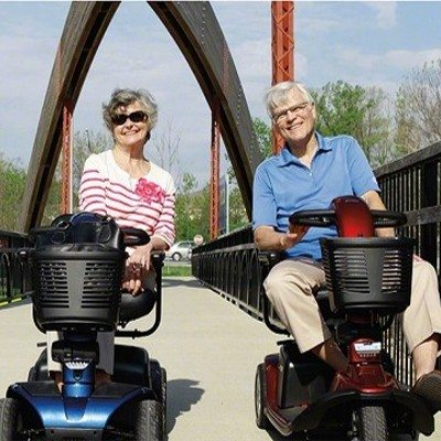 Shop Now or Buy now buttons. Couple both riding mobility scooters on a bridge.