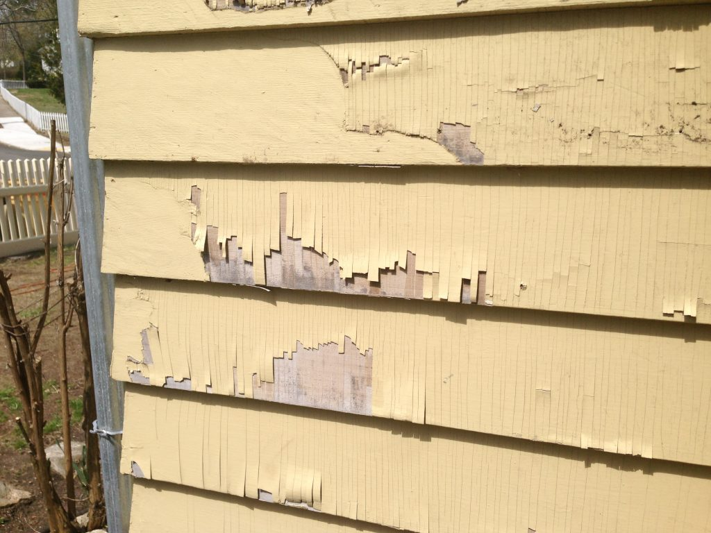 Alligorating paint on the exterior of a new England style home.