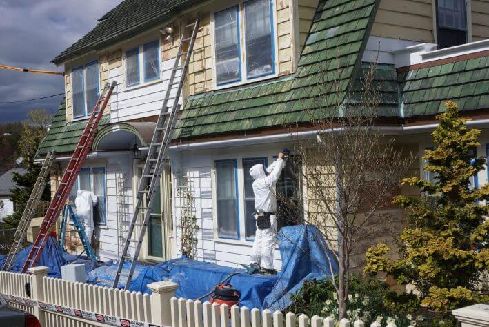 Painters Painting exterior of home before selling it
