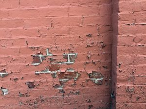 paint peeling off painted brick foundation
