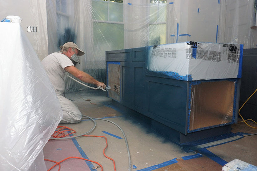 An old man applying blue spray paint on kitchen cabinets