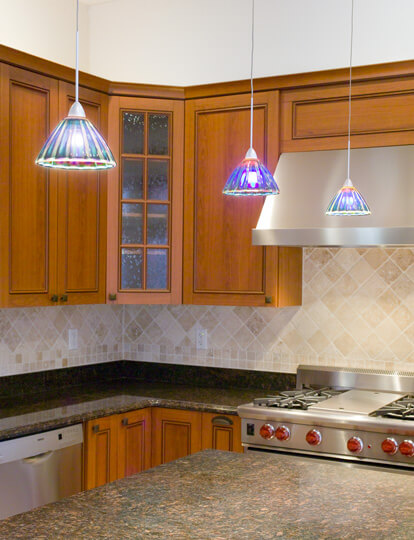 Remodeled kitchen with hanging lights over marble countertops