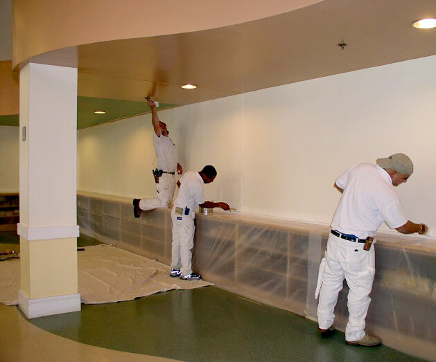 Our crew at work painting on a ceiling and walls
