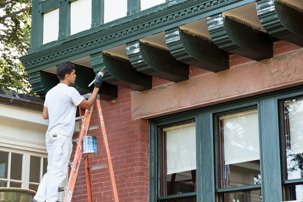 a Catchlight Painting employee paints the historic Bayley House