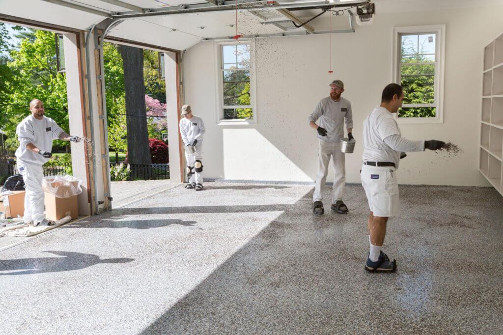 applying second coat of epoxy to garage floor