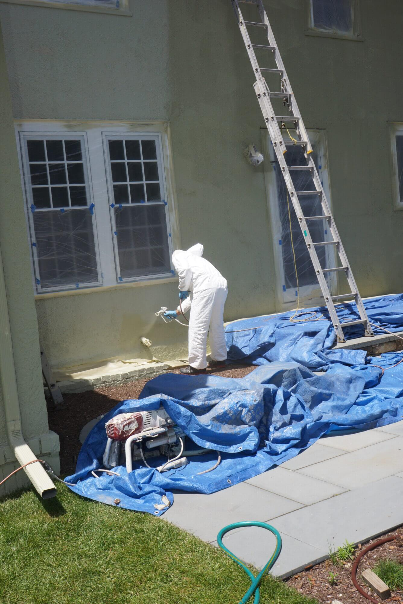 Catchlight employee applying paint to exterior of wall on home
