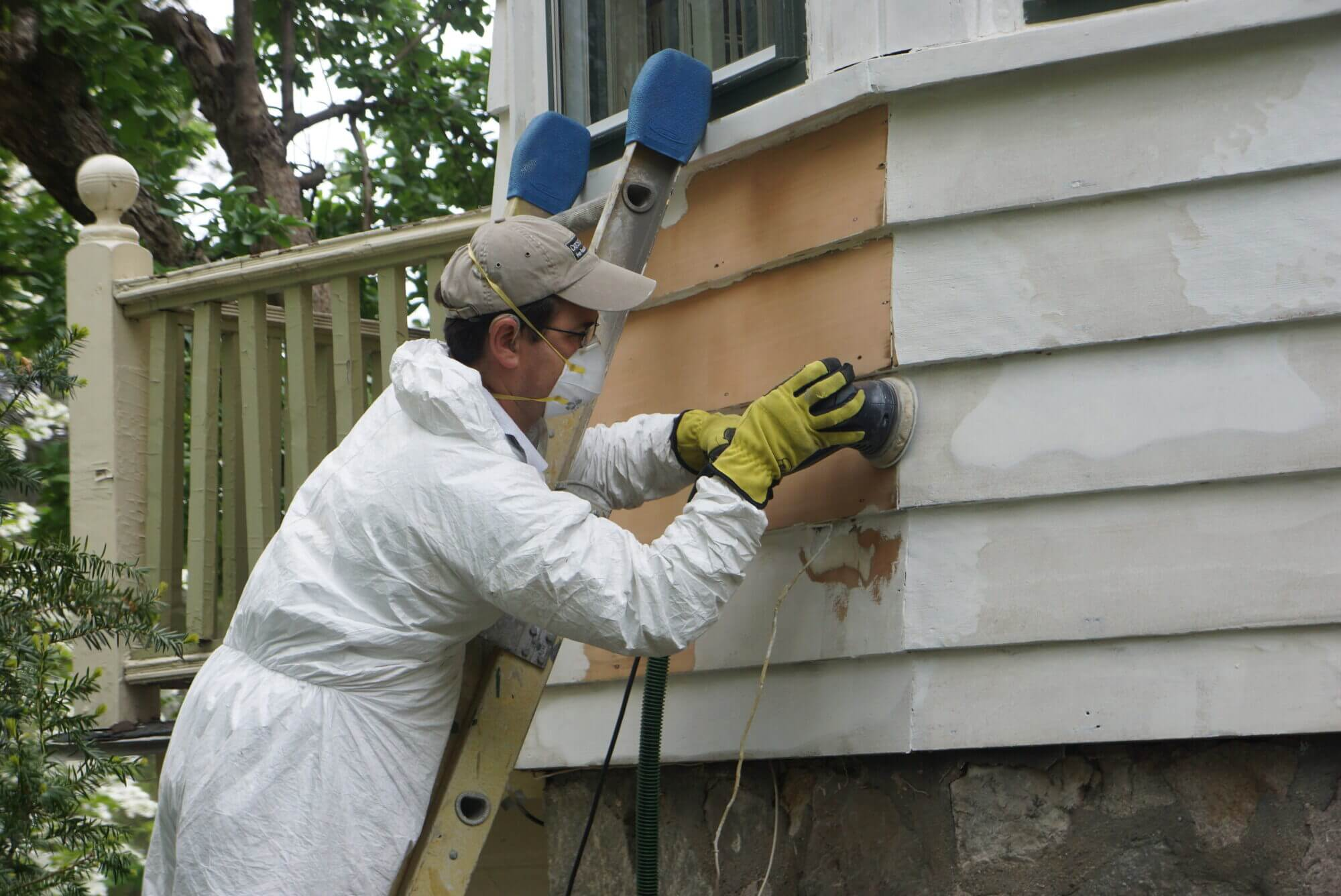 employee using a sander on home exterior