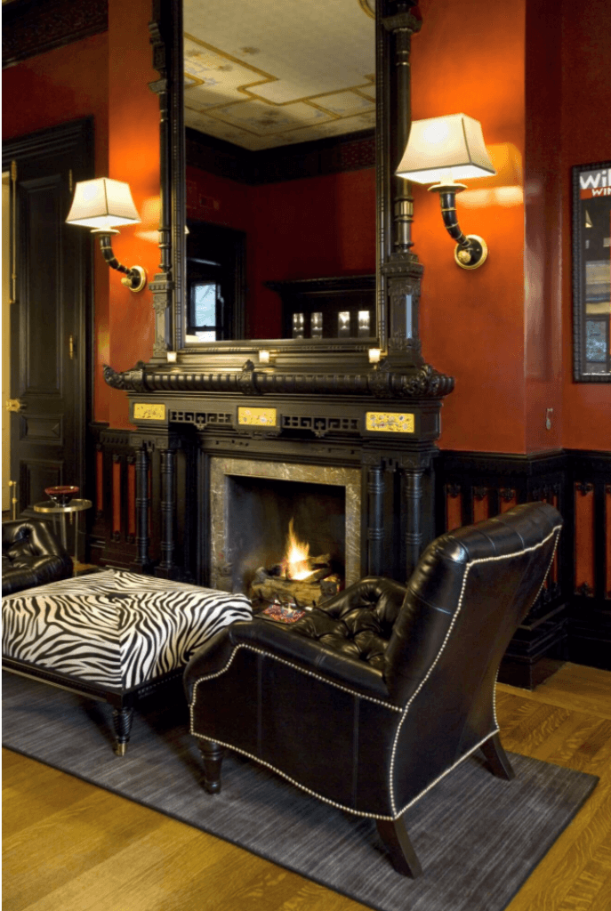 3. view of living room and fireplace with elephant sconces in historic home