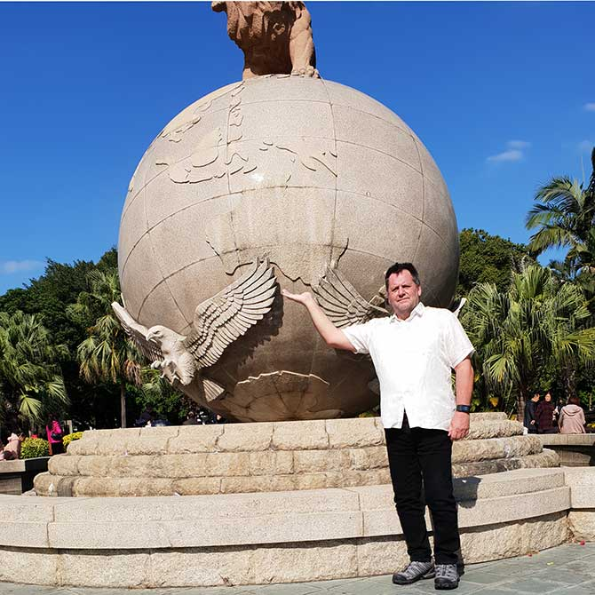 Graham standing in front of a globe showing Australia