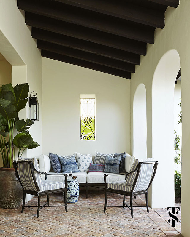 Naples Interior Design Architecture | interior designer & interior architecture by Summer Thornton | outdoor lounge seating in blue and white on a brick patio with curved arches and wood beams - www.summerthorntondesign.com