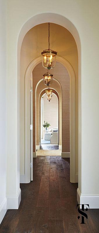 Naples Interior Design by interior designer Summer Thornton   interior architecture of curved doorways through hallway with grasscloth walls and glass lanterns   www.summerthorntondesign.com