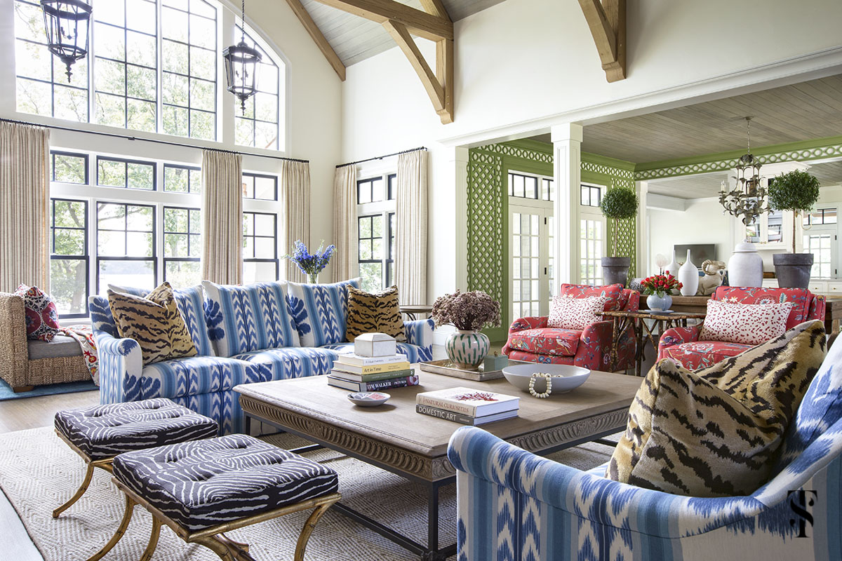 wisconsin lake house interior design by summer thornton with blue ikat sofa in Brunschwig & Fils Chenonceaux, vaulted ceiling with exposed beams and green trellis in background. www.summerthorntondesign.com