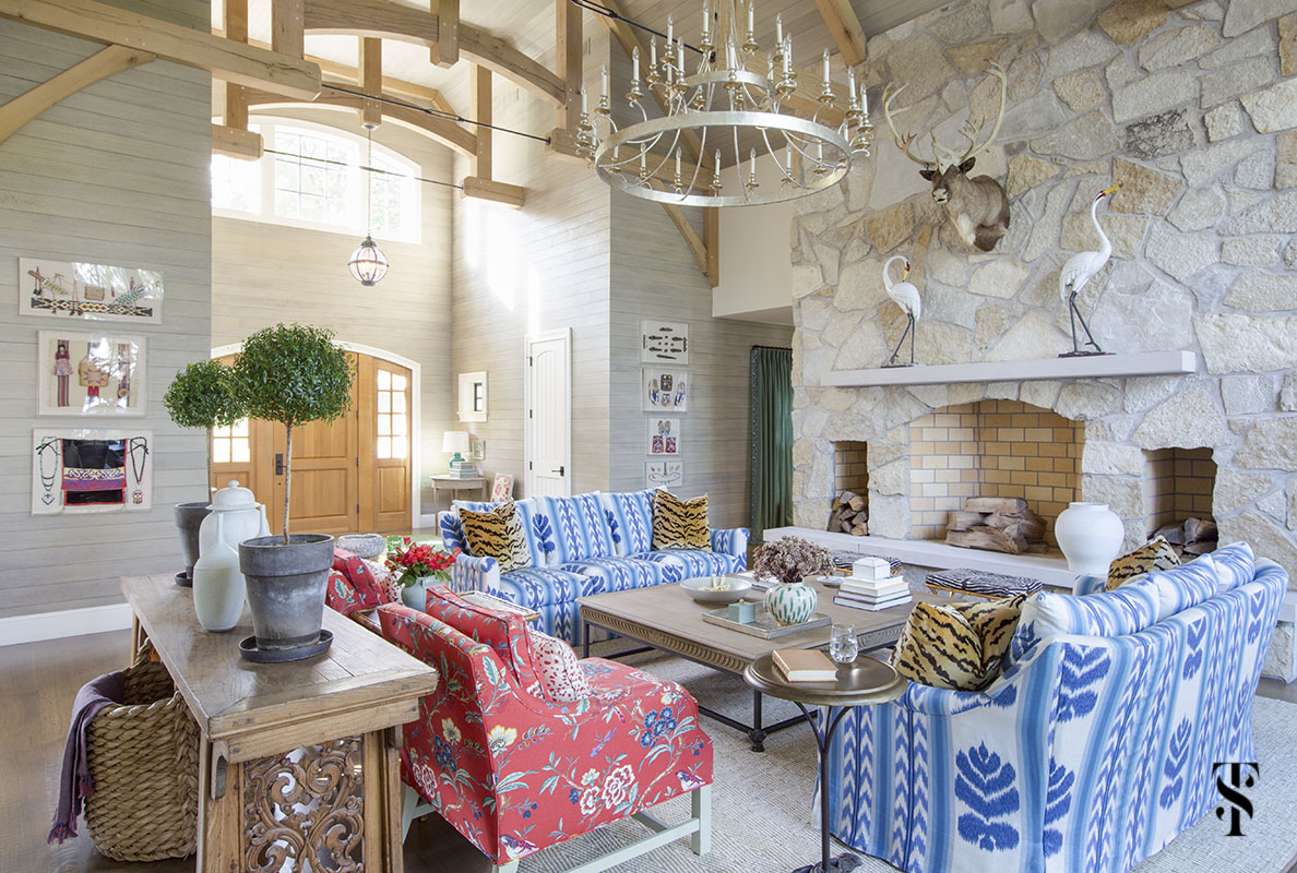 wisconsin lake house interior design by summer thornton with blue ikat sofa in Brunschwig & Fils Chenonceaux, vaulted ceiling with exposed beams and stone fireplace wall with elk taxidermy. www.summerthorntondesign.com