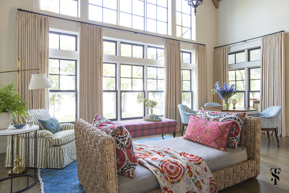 wisconsin lake house interior design by summer thornton with jute daybed, ethnic pattern pillows, and game table overlooking the lake through a wall of windows. www.summerthorntondesign.com
