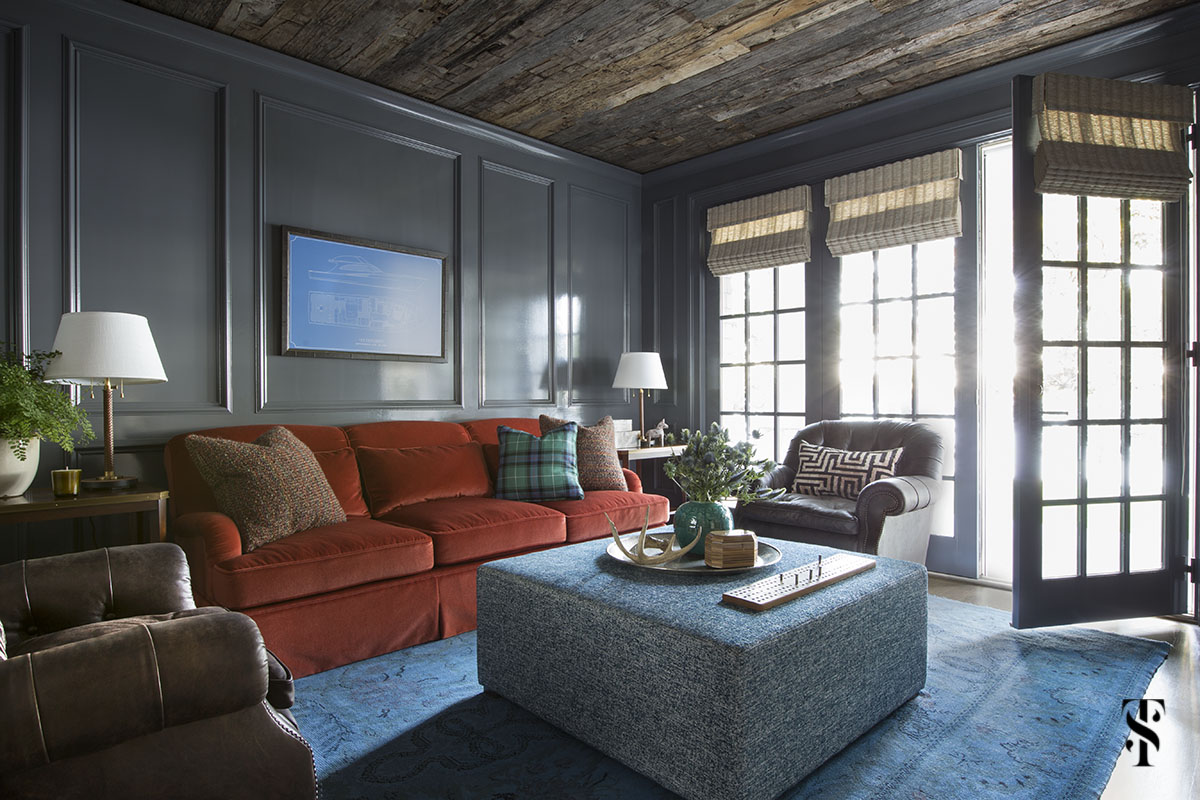 high gloss den with orange sofa, blue overdye rug and wood ceiling; interior design by summer thornton www.summerthorntondesign.com