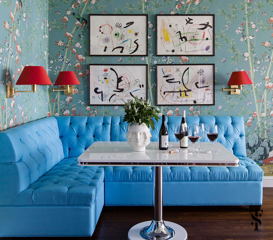 Breakfast & dining area designed by Summer Thornton featuring F Schumacher Miles Redd Brighton Pavillion wallpaper, red sconce shades, Joan Miro artwork and a bright blue banquette. Summer Thornton Interior Design works on projects nationwide from her Chicago interior design office headquarters.