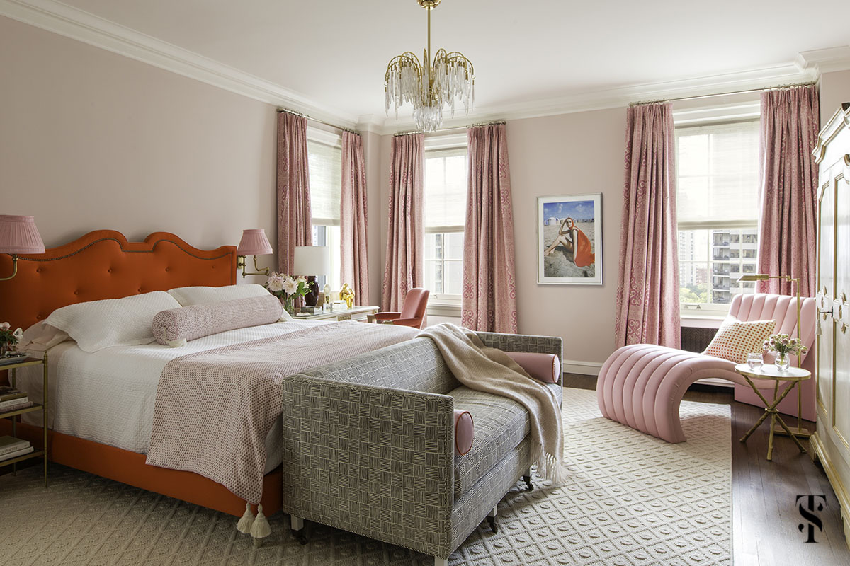 Pink and red bedroom with tufted red headboard, pink walls, brass sconces, and vintage chandelier. Interior design by Summer Thornton Design in Chicago.
