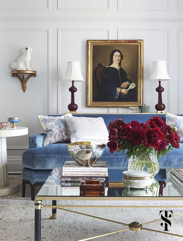 A remodel of a luxury condo at the Palmolive Building in Chicago by Summer Thornton. A fresh coat of paint, Farrow & Ball's Blackened, provides a bright backdrop for high-shine accents, rich blue velvets, and warm wood tones in the living room designed by Summer Thornton. Sofa, chairs, and round library table, Baker. Settee, Ferrell Mittman. Cocktail table, Old Plank. Alabaster pendant light and brass side table, Vaughan. For more photos visit www.SummerThorntonDesign.com. (as seen in House Beautiful, January 2019)