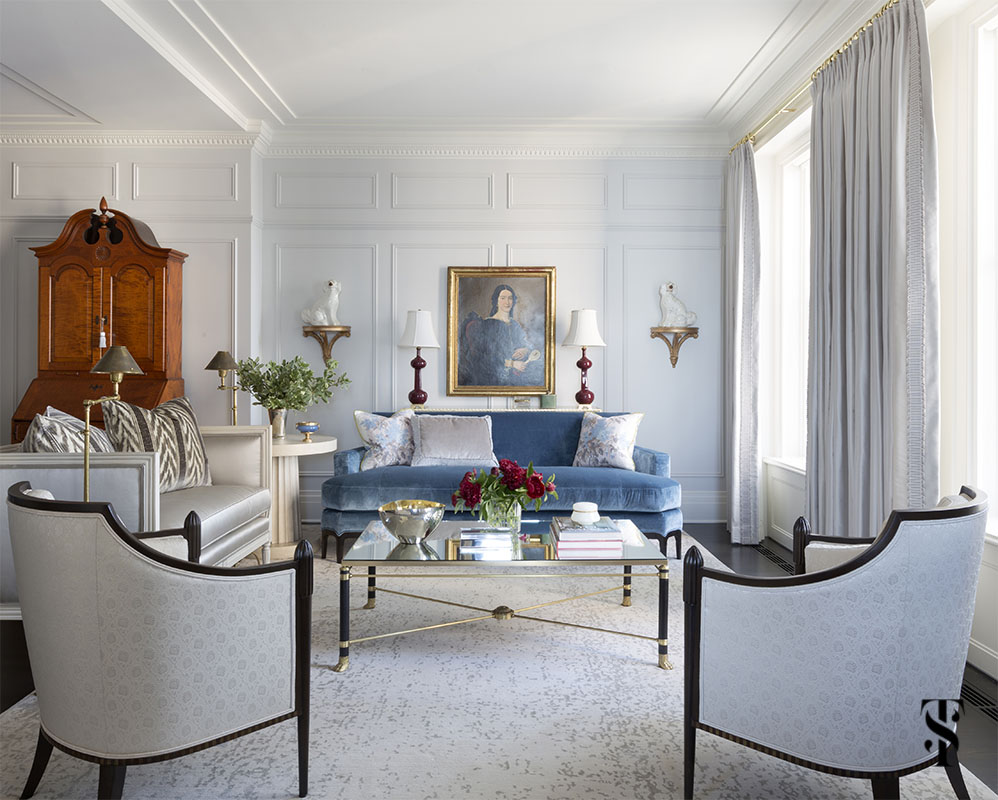 formal living room with blue silk velvet sofa, staffordshire dogs and oil portraiture, interior design by Summer Thornton in Chicago's Palmolive building. For more photos, visit www.SummerThorntonDesign.com
