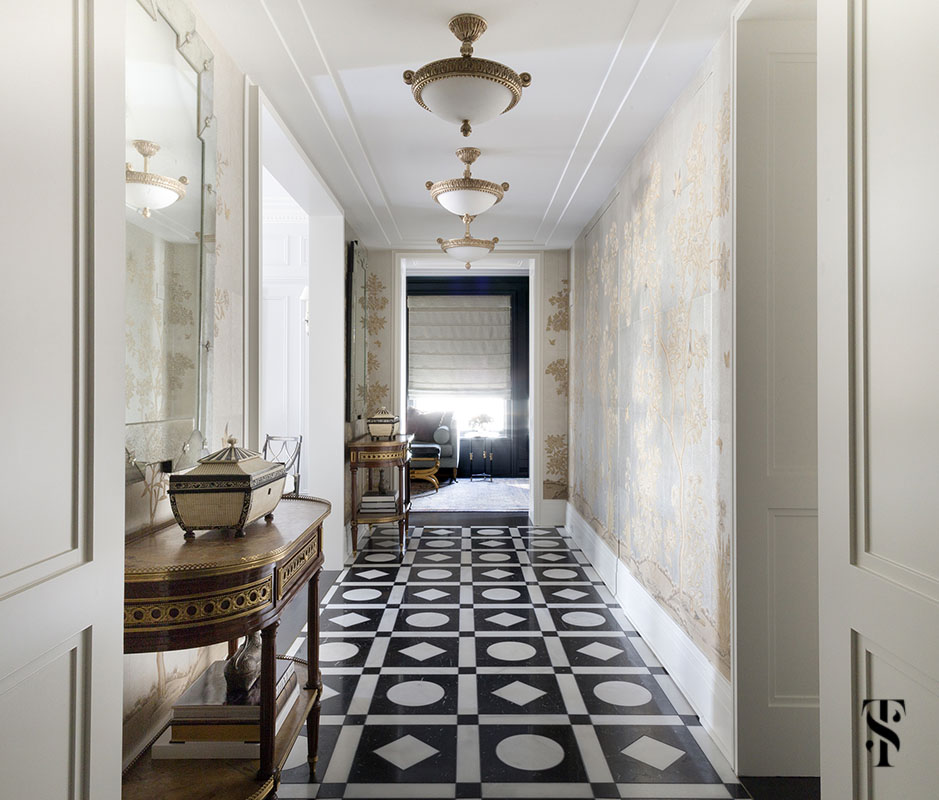 An exceptional graphic marble black and white floor in a hallway of Gracie wallpaper as designed & renovated by Summer Thornton for a condo in Chicago's Palmolive Building. For more photos visit www.SummerThorntonDesign.com.