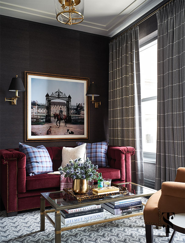 A masculine office with deep raspberry tufted club sofa, dark grey grasscloth, and geometric rug as designed by Summer Thornton in Chicago's Palmolive Building. For more photos visit www.SummerThorntonDesign.com.