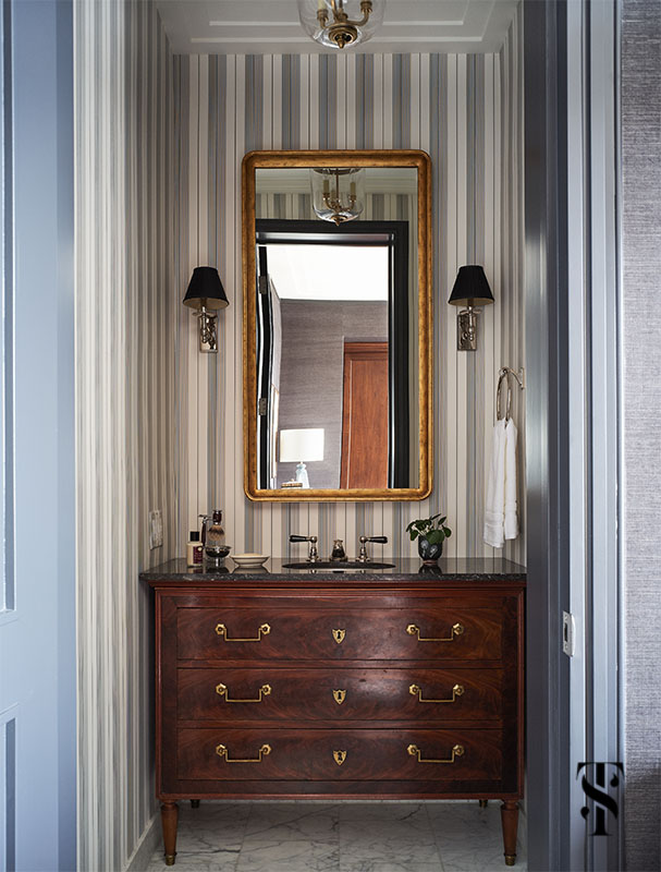 A masculine bathroom with black and white striped wallpaper and antique chest as vanity designed by Summer Thornton. For more photos visit www.SummerThorntonDesign.com