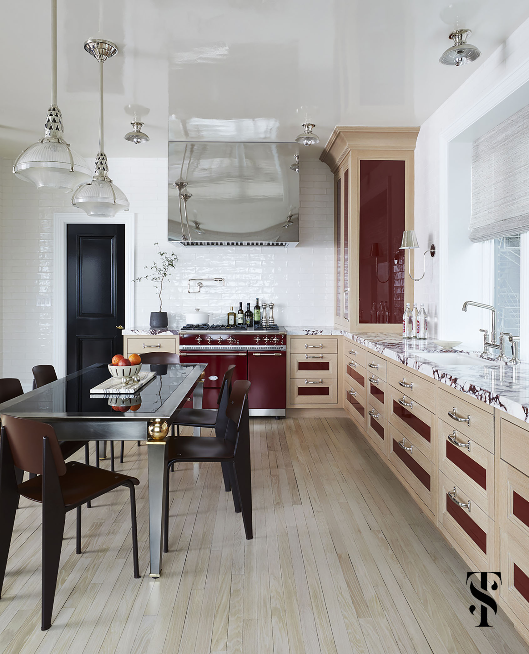 glossy details from a mirror-finish polished stainless steel hood to high-gloss cabinetry inserts in burgundy red & even a lacquered ceiling give this kitchen by interior designer Summer Thornton a water-like reflective quality, emulating the waves of Lake Michigan that it overlooks