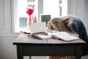 Woman exhibiting performance issues by laying head on desk.